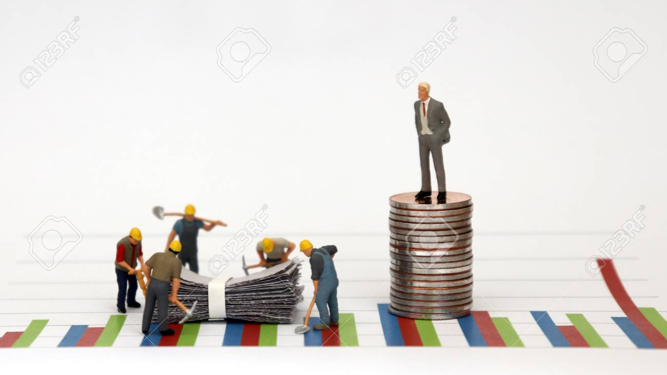 A man dressed in a suit standing on top of a pile of coins against a graph and miniature workers at a construction site below it. - 101194315