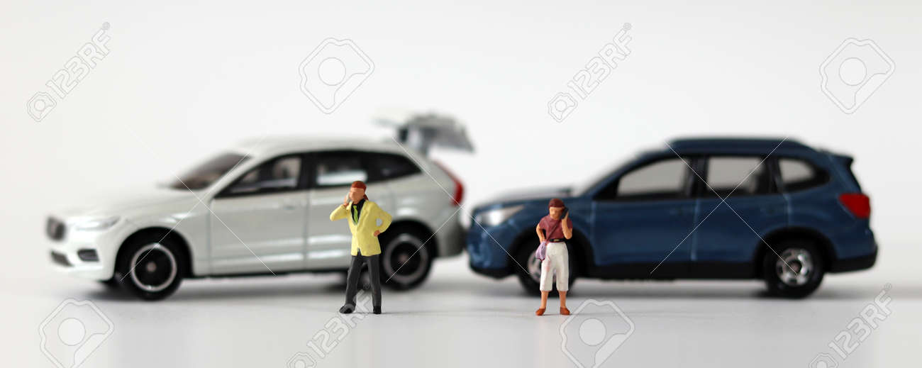 Two miniature cars collided and two miniature people calling. Concepts about car accidents and miniature people. - 167565151