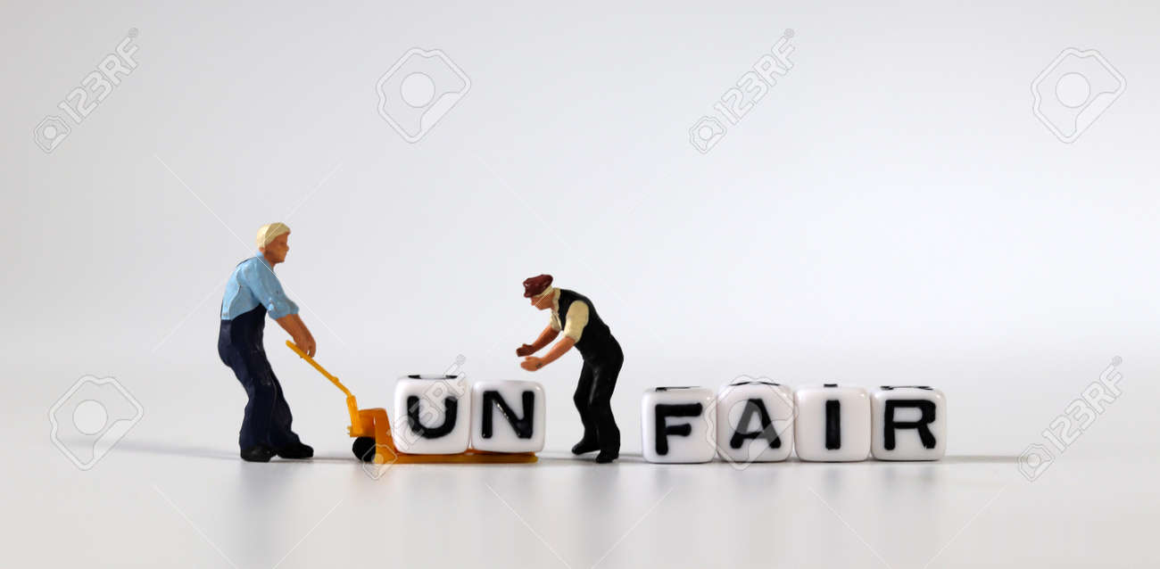 Two miniature men moving the cube of'UN' word from cube with'FAIR' word to cart. White cube with words and miniature people. - 167841722