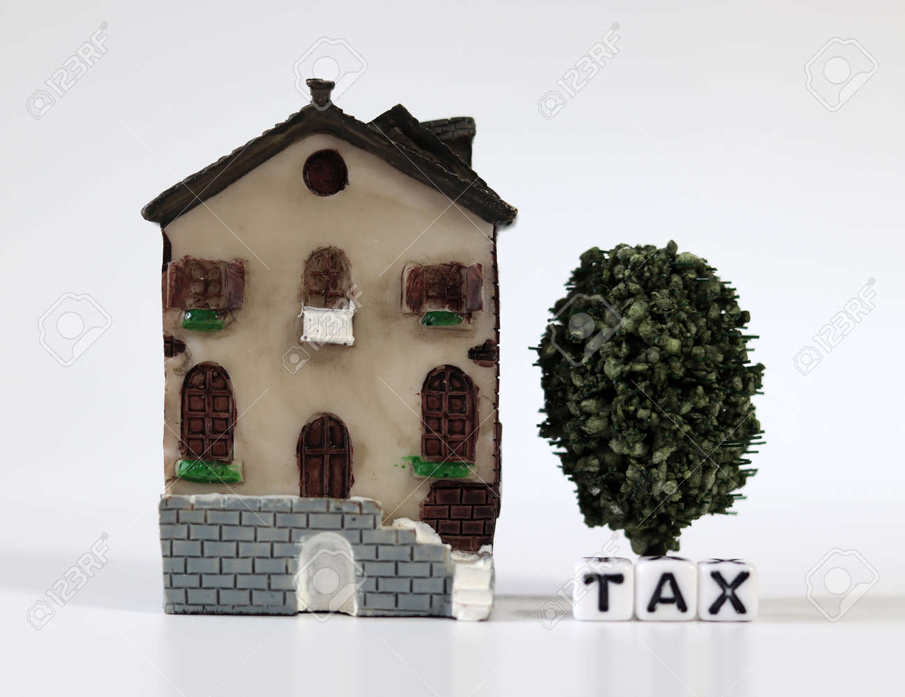 A white cube with the word'TAX' with a miniature house. The concept of increasing real estate taxes. - 167841723