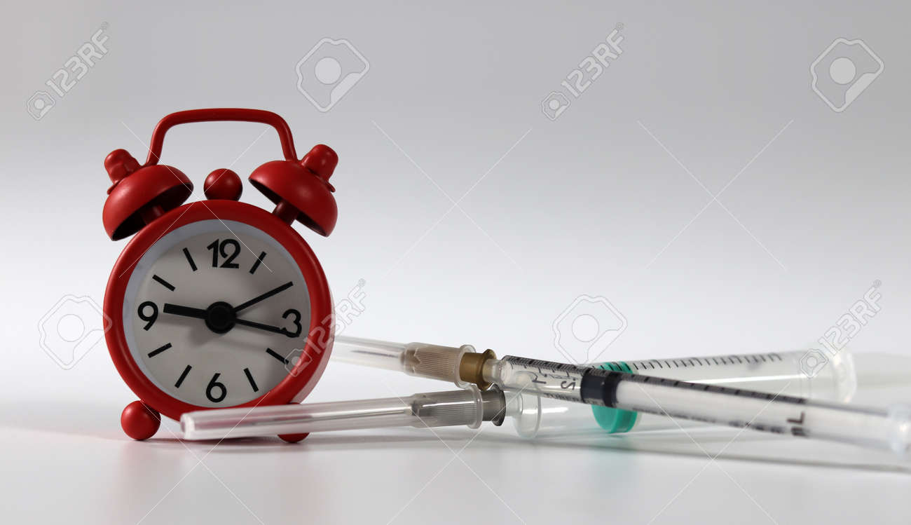 Syringe and a red alarm clock. Concept of the importance of vaccination. - 169516254