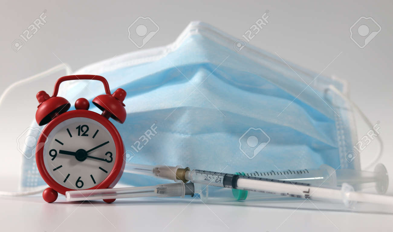 Syringe and mask with a red alarm clock. Concept of the importance of vaccination. - 169516497