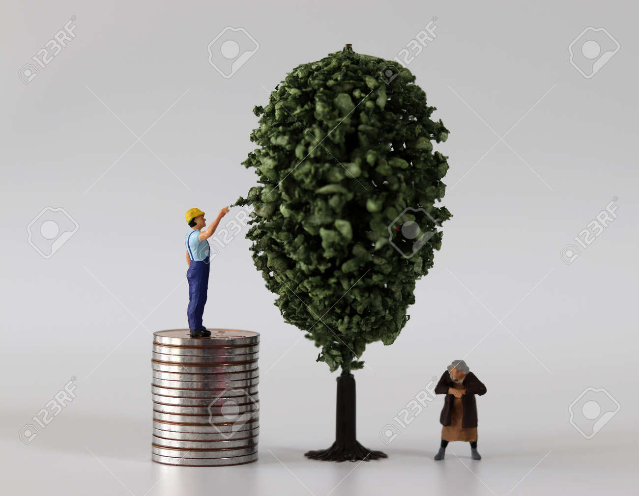 A miniature man and a miniature woman on a pile of coins next to a miniature tree. The concept of economic inequality. - 169818822