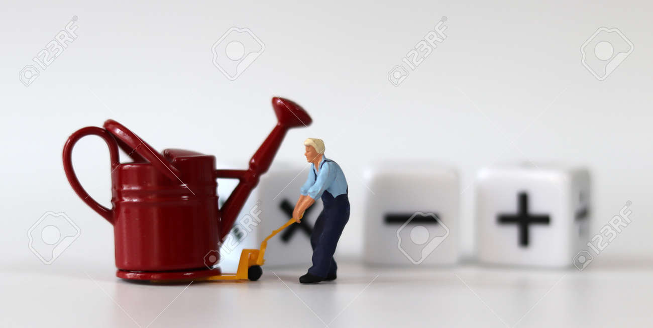 A miniature man carrying a red watering can with a handcart and a white cube with arithmetic symbols. Miniature people and business concept. - 170031992