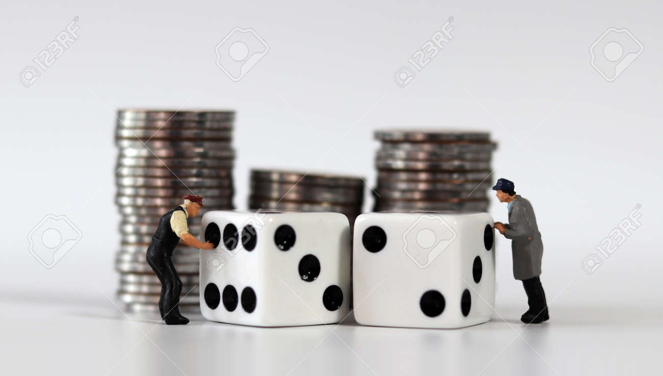 Pile of coins and two white dice. Miniature people and business concept. - 170214198