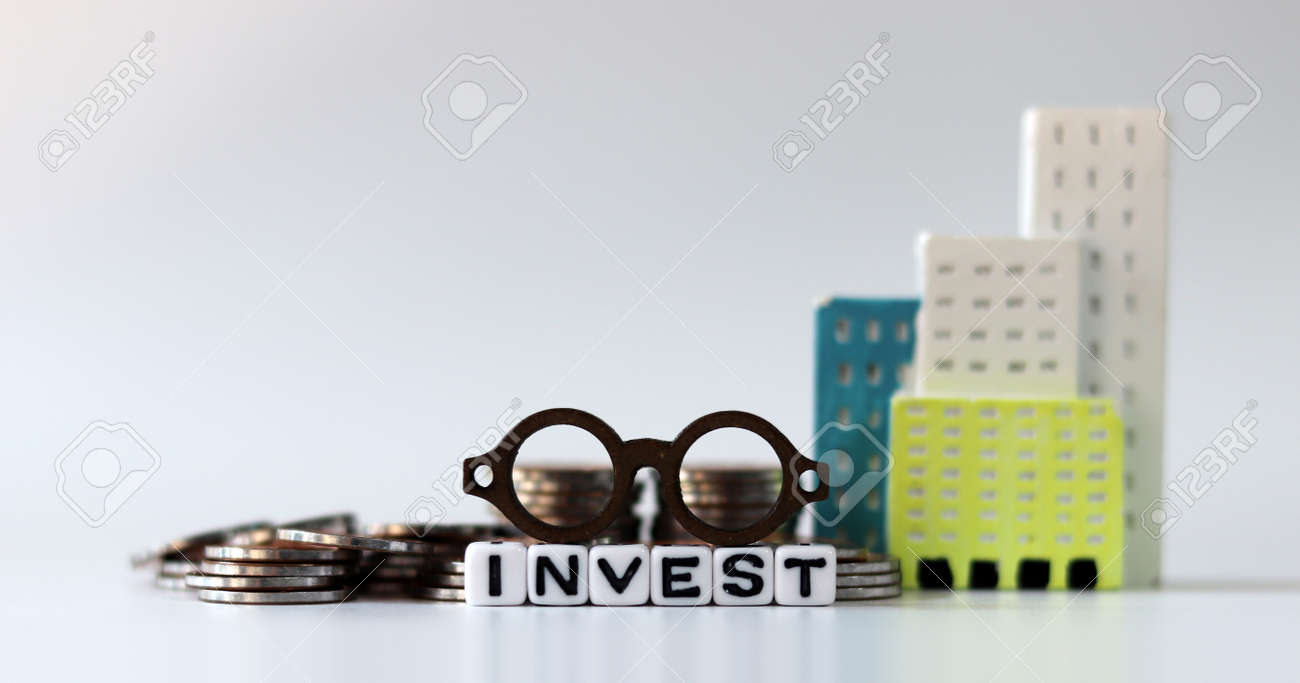 A miniature eyeglasses on White cube bearing the word 'INVEST' with a bundle. The concept of real estate investment. - 172030560