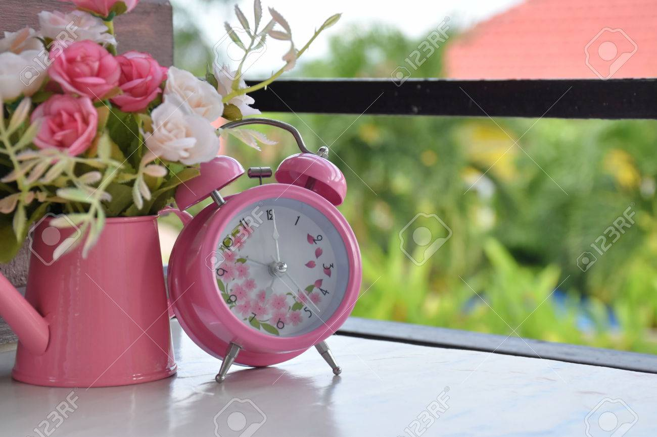 pink alarm clock and rose flowers in vase on white table in stock