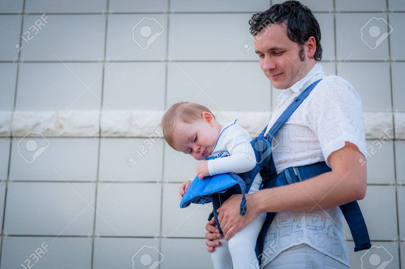 Image Of Young Father And His Asleep Baby Walking In Baby Carrier