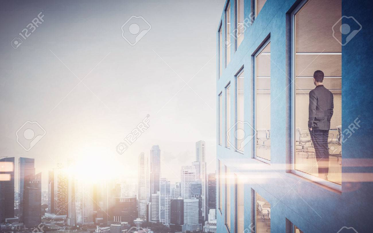 Businessman inside skyscraper, lookng at the city through the window. - 50793214