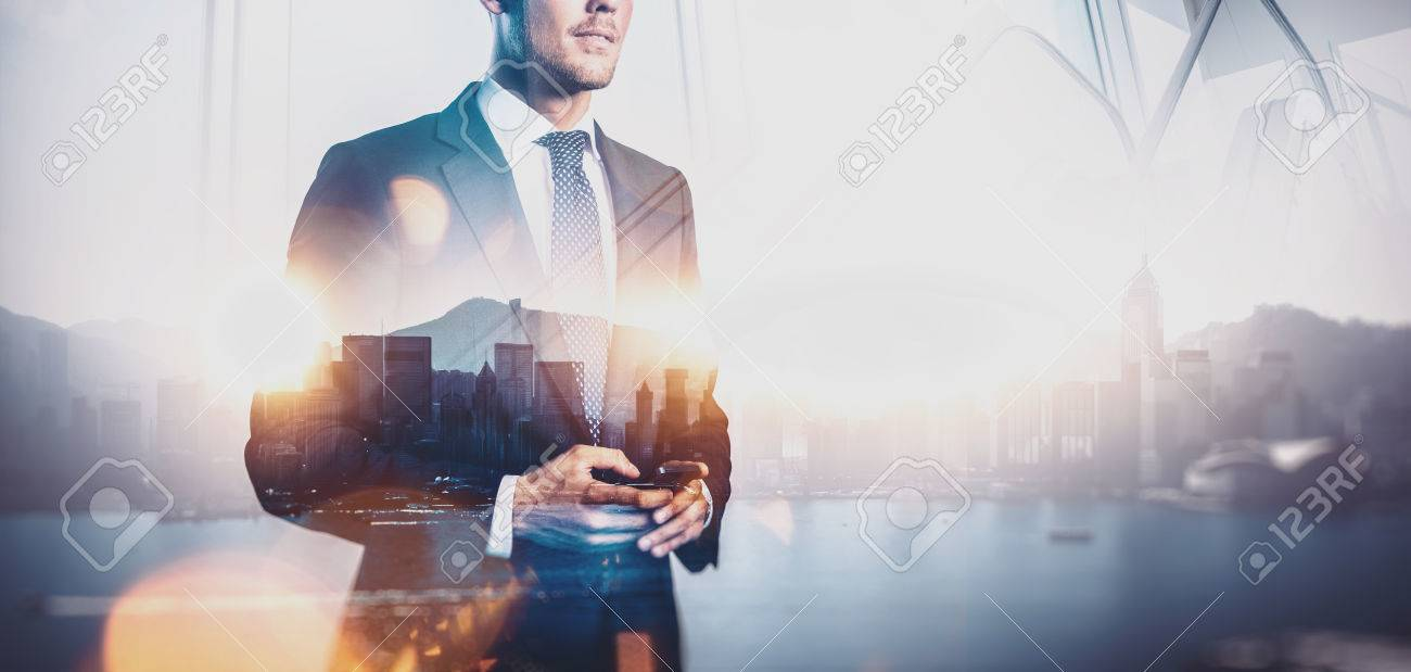 Photo of businessman holding smartphone. Double exposure photo of panoramic city view at sunrise - 52908168