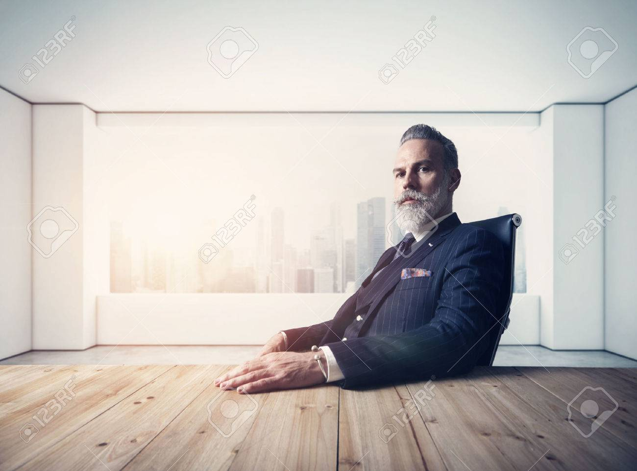 Portrait of adult businessman wearing trendy suit and sitting modern loft on leather chair against the panoramic window with city view. - 52908232
