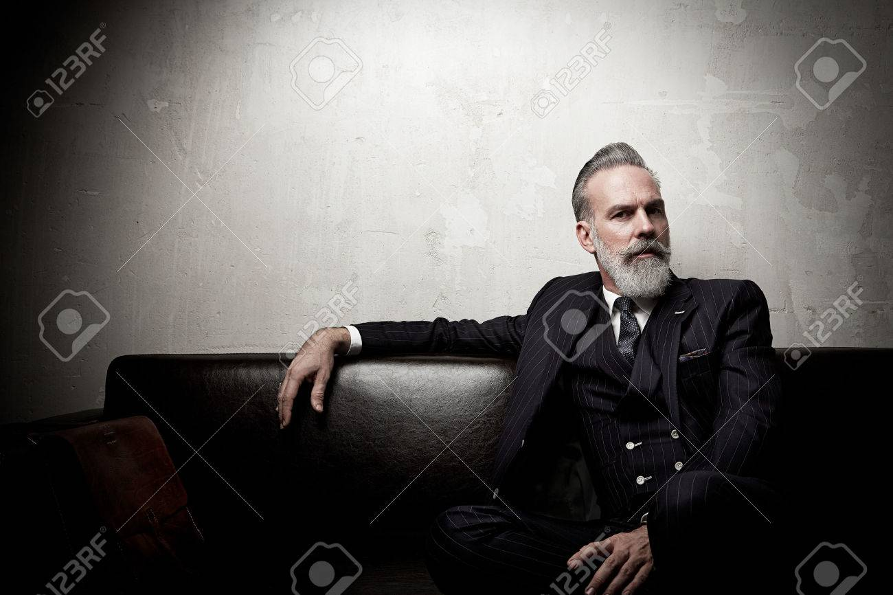 Portrait of adult businessman wearing trendy suit and sitting modern studio on leather sofa against the empty wall. - 52908240