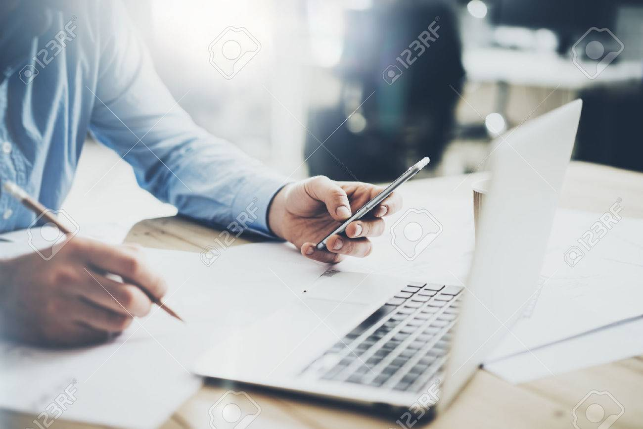Businessman in workplace. Texting message smartphone and holding pencil hand. Generic design notebook wood table. Horizontal mockup, - 52908253
