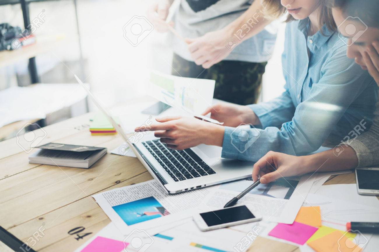 Creative team coworking project.Photo business managers working with new startup in modern loft.Analyze reports,plans. Notebook on wood table, papers, documents, statistics. - 54418869