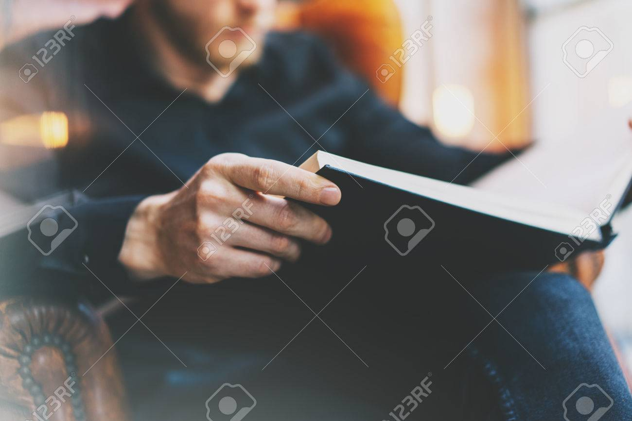 Portrait handsome bearded man wearing glasses black shirt.Man sitting in vintage chair university library, reading book and relaxing. Blurred background. Panoramic windows, film effect. - 54433012