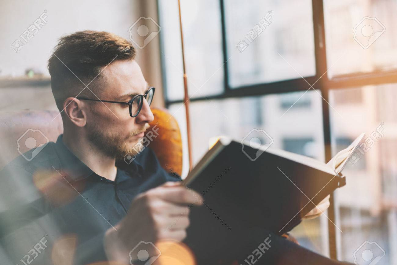 Portrait handsome bearded businessman wearing black shirt.Man sitting in vintage chairmodern loft studio, reading book and relaxing. Blurred background, film effect. - 54433015