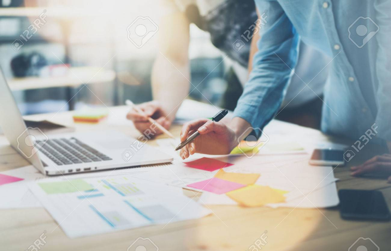 Team work process.Photo young business managers crew working with new startup project.Notebook on wood table, typing keyboard.Using modern smartphones, texting message, analyze plans. - 54558474