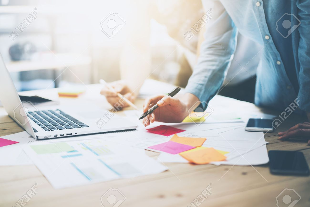Photo coworking team meeting. Young business crew working with new startup project in studio. Modern notebook on wood table. Using marketing plans,sales reports. Horizontal - 54818733