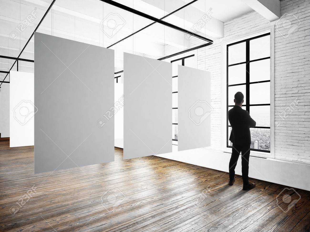 Businessman Modern museum expo loft interior.Open space studio.Empty white canvas hanging.Wood floor,bricks wall,panoramic windows.Blank frames ready for bussiness information.Horizontal mockup - 58177524