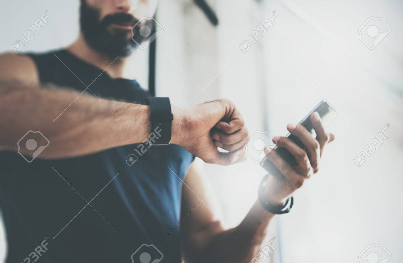 Close-up Shot Bearded Sportive Man After Workout Session Checks Fitness Results Smartphone.Adult Guy Wearing Sport Tracker Wristband Arm.Training hard inside gym.Horizontal bar background.Blurred - 64805301