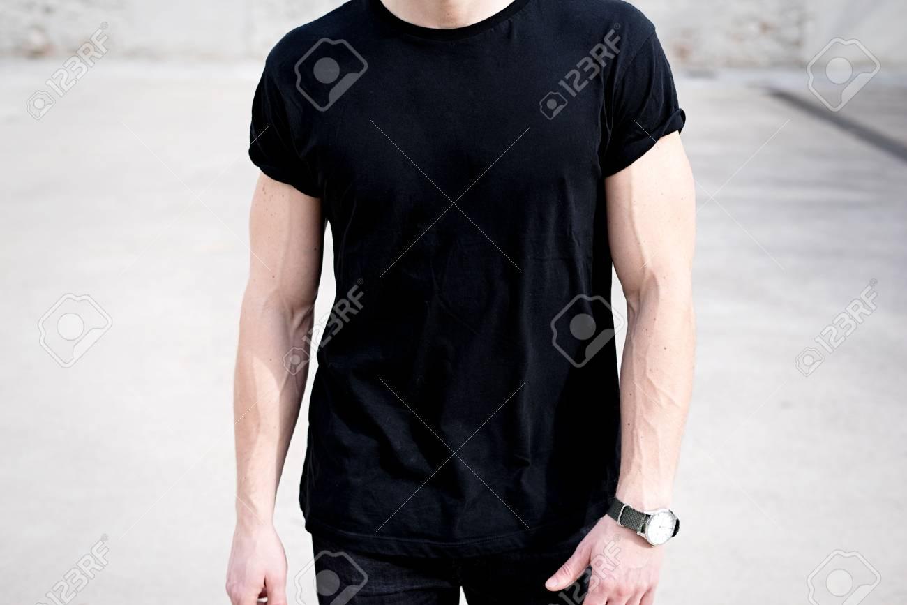 235174f434119 Foto de archivo - Opinión del primer del hombre muscular joven que desgasta  la camiseta y los pantalones vaqueros negros que presentan afuera. Fondo  vacío.