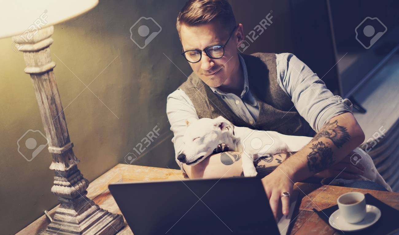 3187d0ddd Handsome tattooed man in eyeglasses working at home on laptop while sitting  at the wooden table