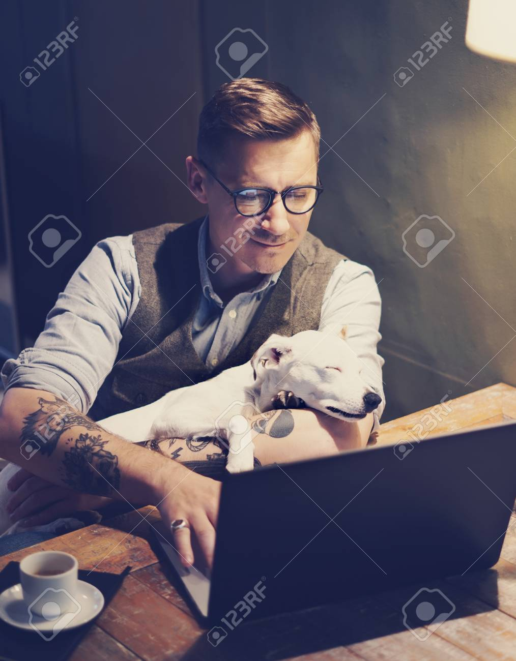e6d7ce5ad Smiling tattooed man in eyeglasses working at home on laptop while sitting  at the wooden table
