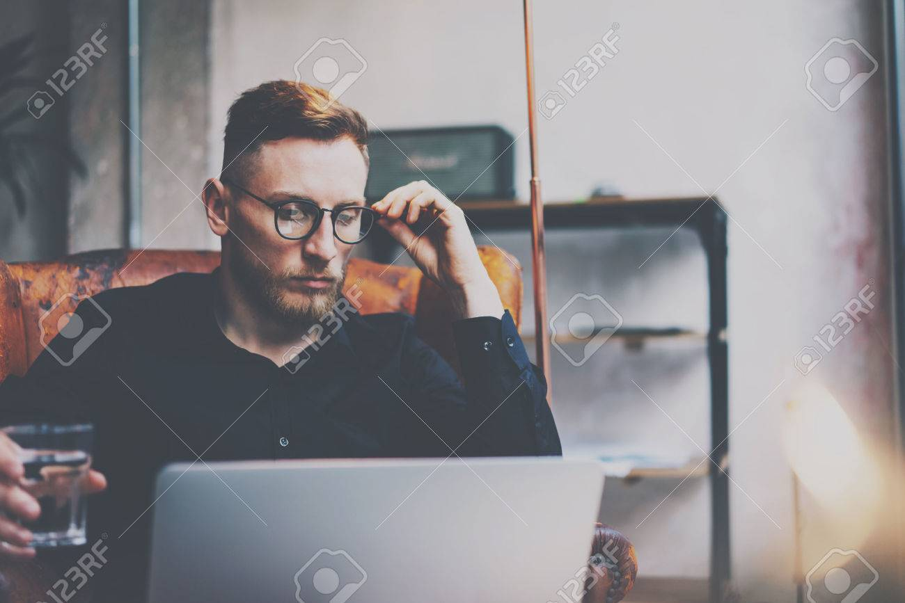 Pensive bearded businessman in eyeglasses working at modern loft.Man sitting in vintage chair,holding in hands glass of water,using contemporary notebook.Blurred background,flares.Horizontal Standard-Bild - 74623612