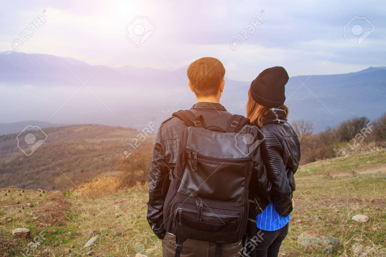 A guy with a backpack and a girl looking at the mountains in the distance, the concept of tourism. - 155637185