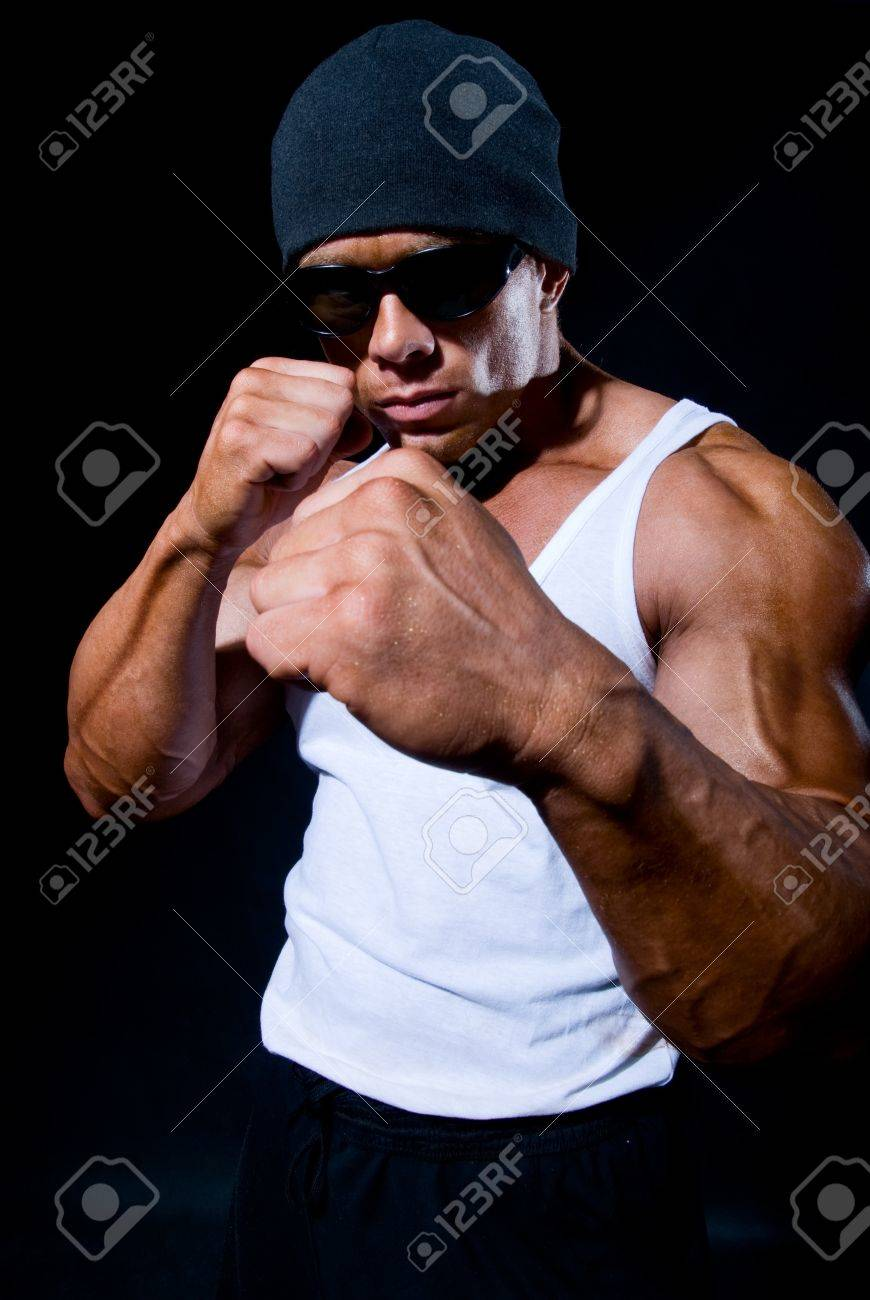 The strong sports person in a boxing rack and in dark glasses on a black background Stock Photo - 11783406