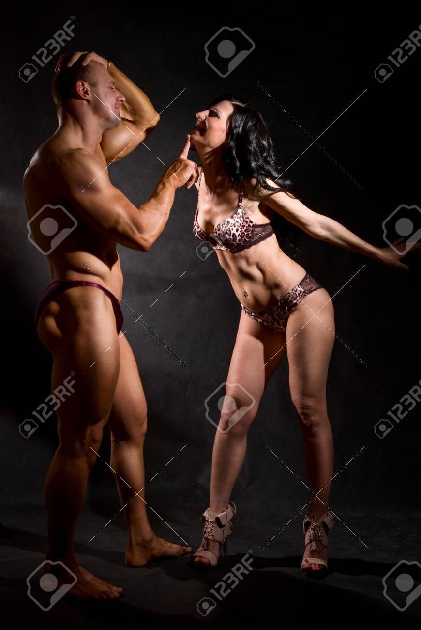 Muscular man and a woman posing in studio on dark background Stock Photo - 16306357