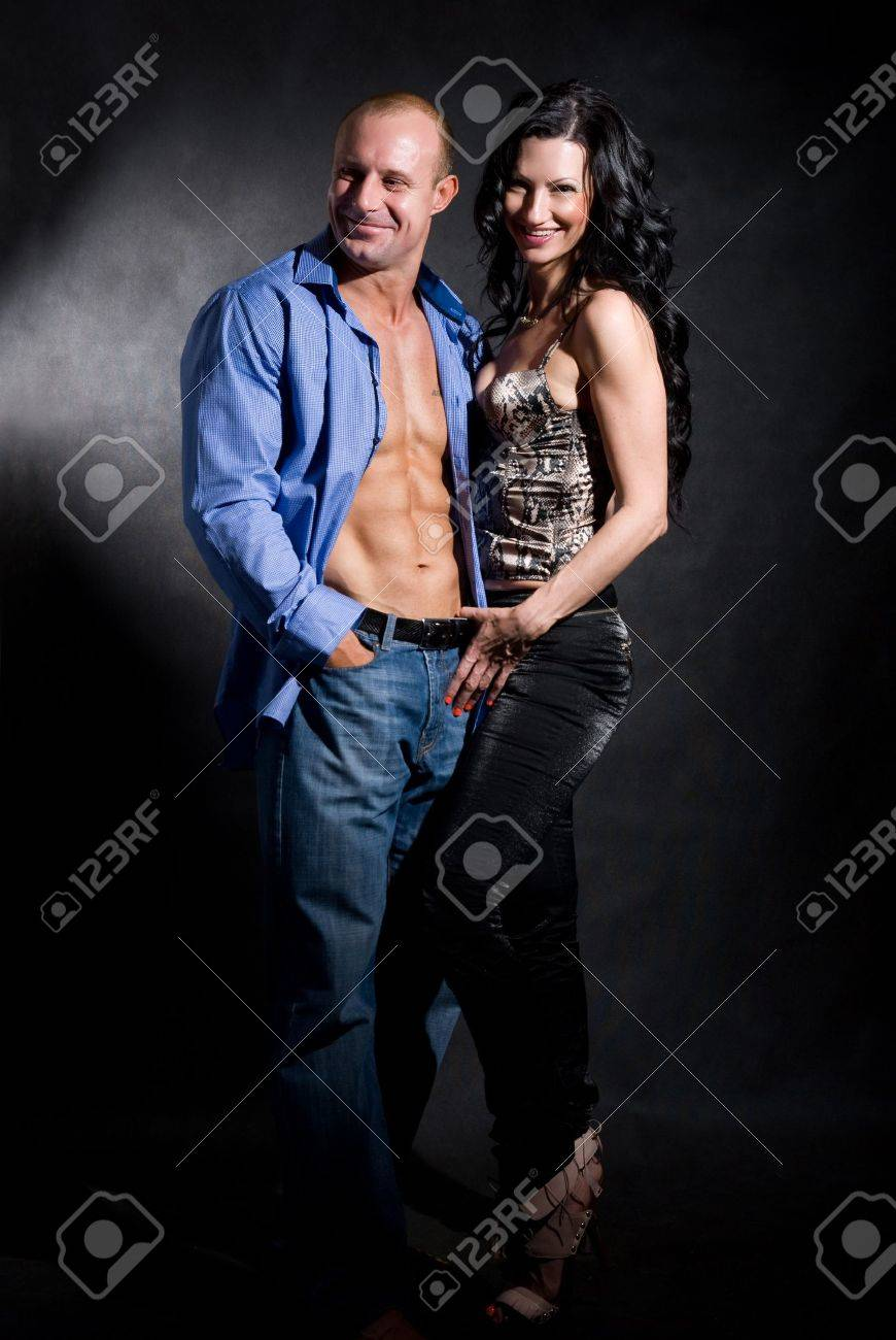 Muscular handsome sexy man with pretty woman on dark background Stock Photo - 16306366