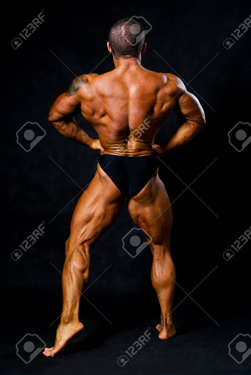 Tanned Bodybuilder Shows Muscles Of Arms And Back In Black Studio