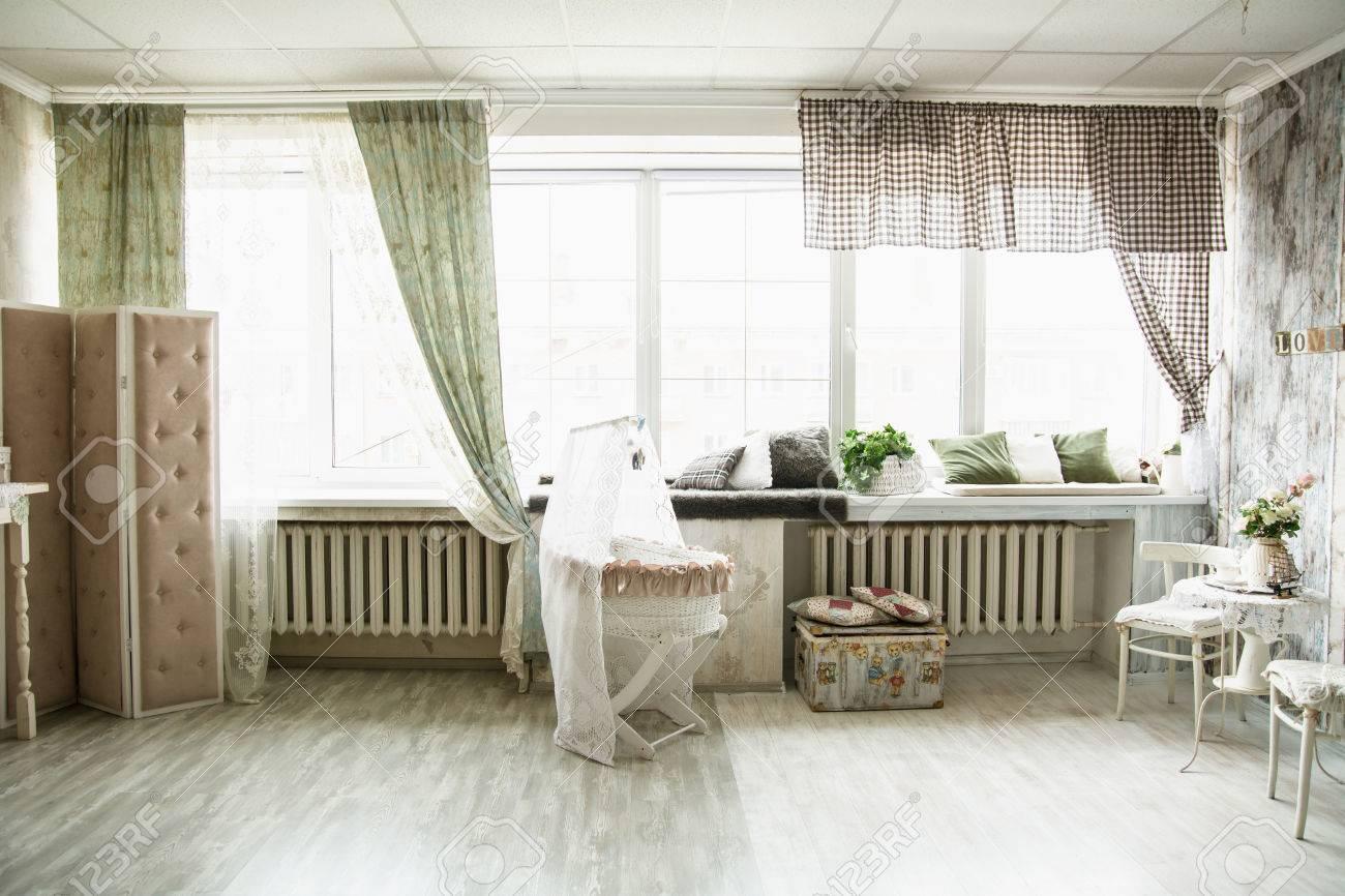 Davanzale Interno Della Finestra interni in stile retrò stanza luminosa con un lettino e grandi finestre.  cuscini sul davanzale della finestra e sul petto per bambini su un piano di