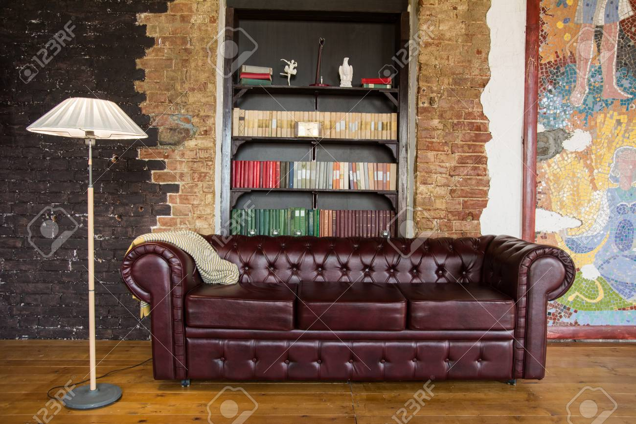 Interior of the room in old style with a leather sofa. Bookshelf..