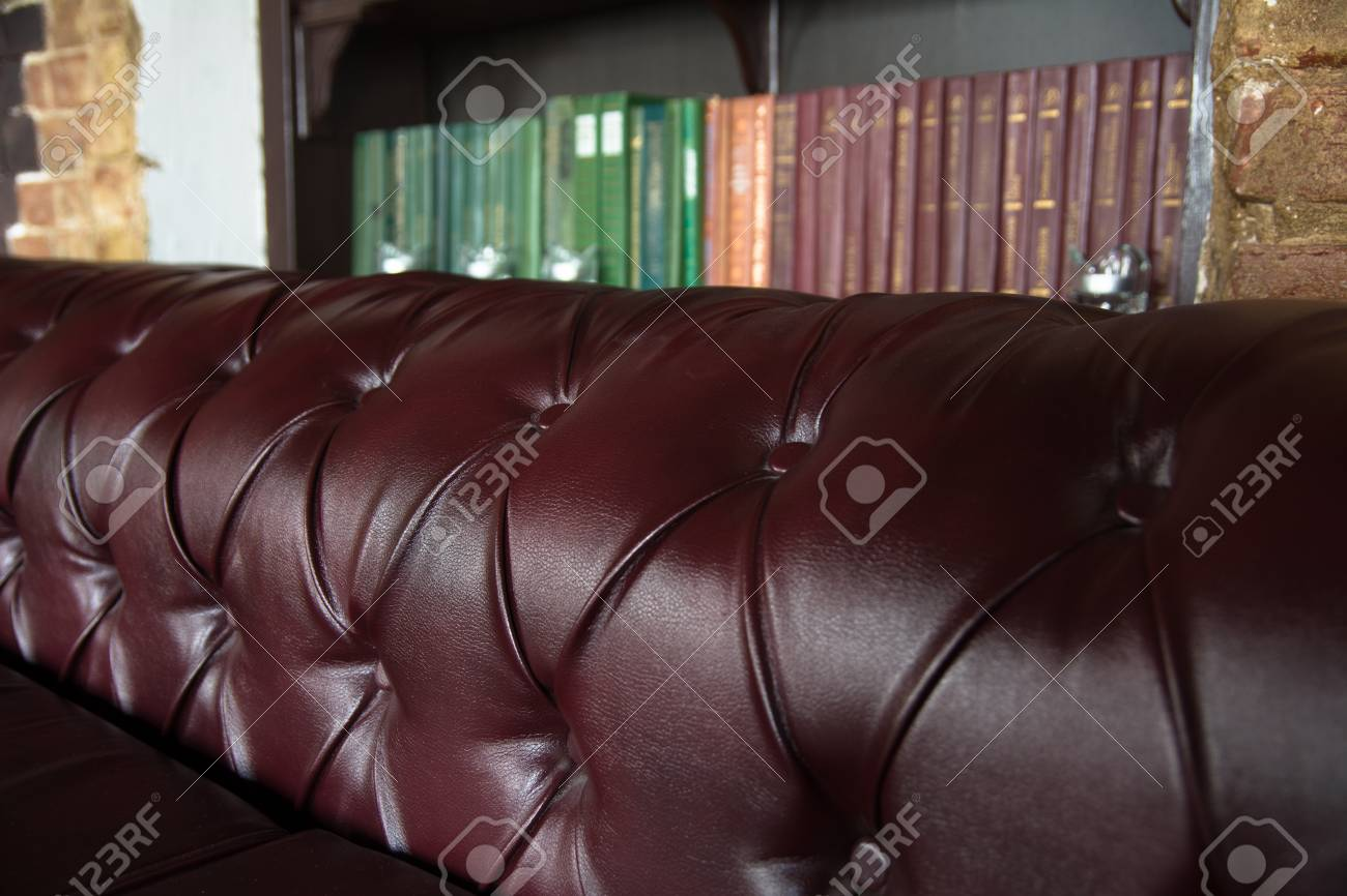 Background close-up burgundy leather sofa and bookshelf.
