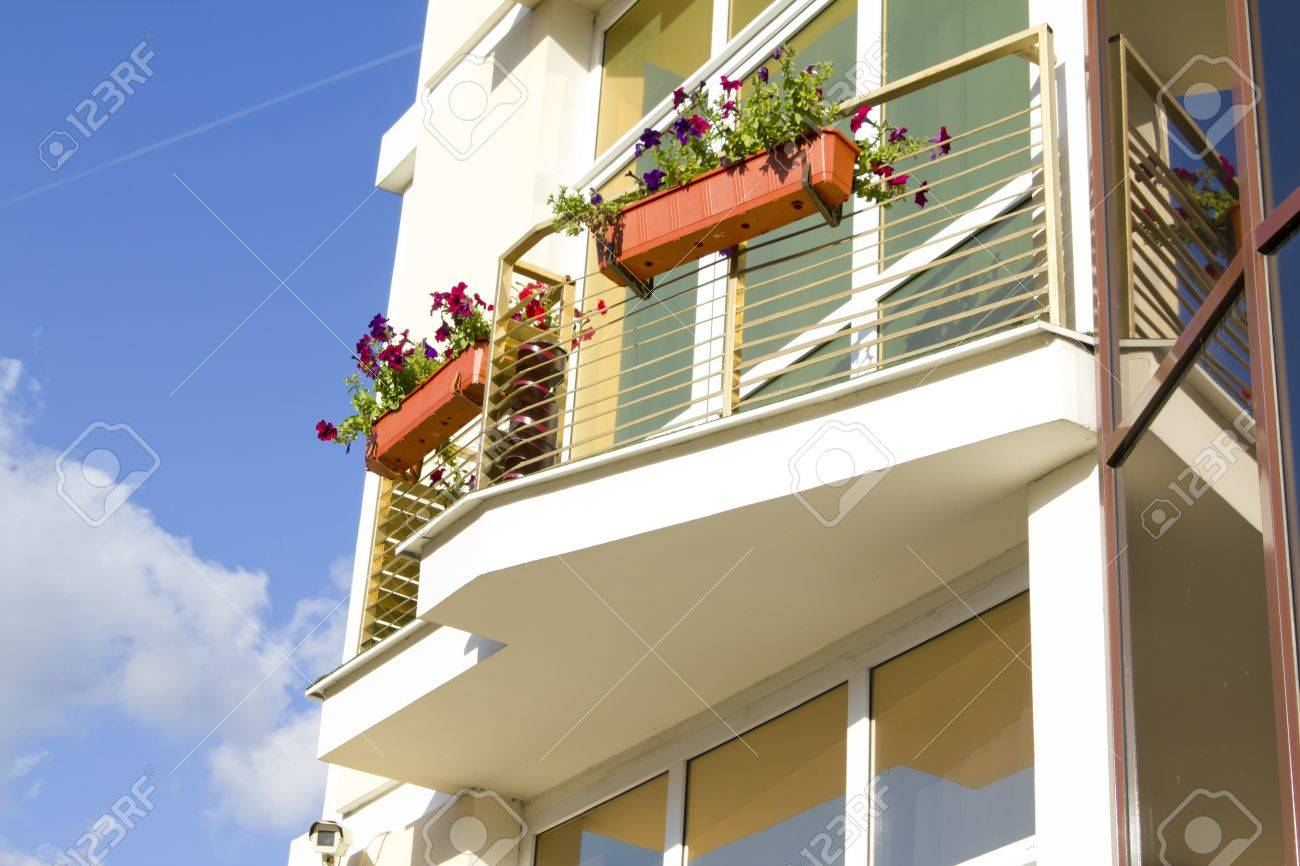 Balcony With Petunia Flowers On Modern Apartments Building Stock