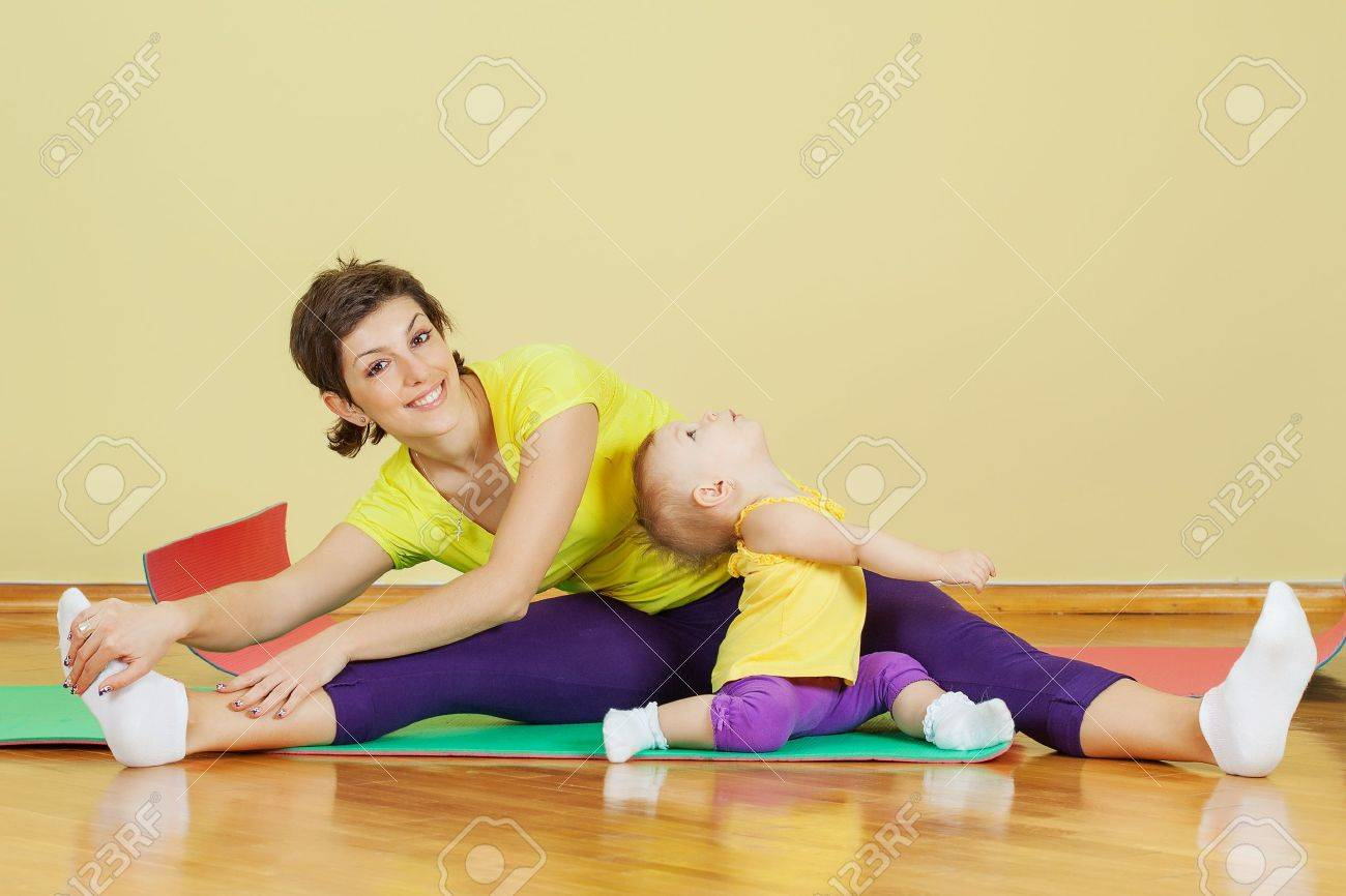 Mother do phisical exercises with her daughter at home - 21001109