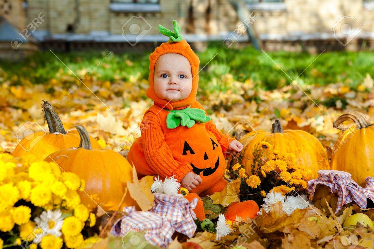 Child in pumpkin suit on background of autumn leaves - 22011091