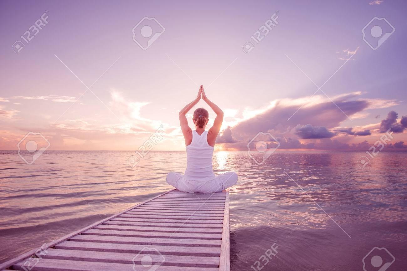 Caucasian woman practicing yoga at seashore - 22228288