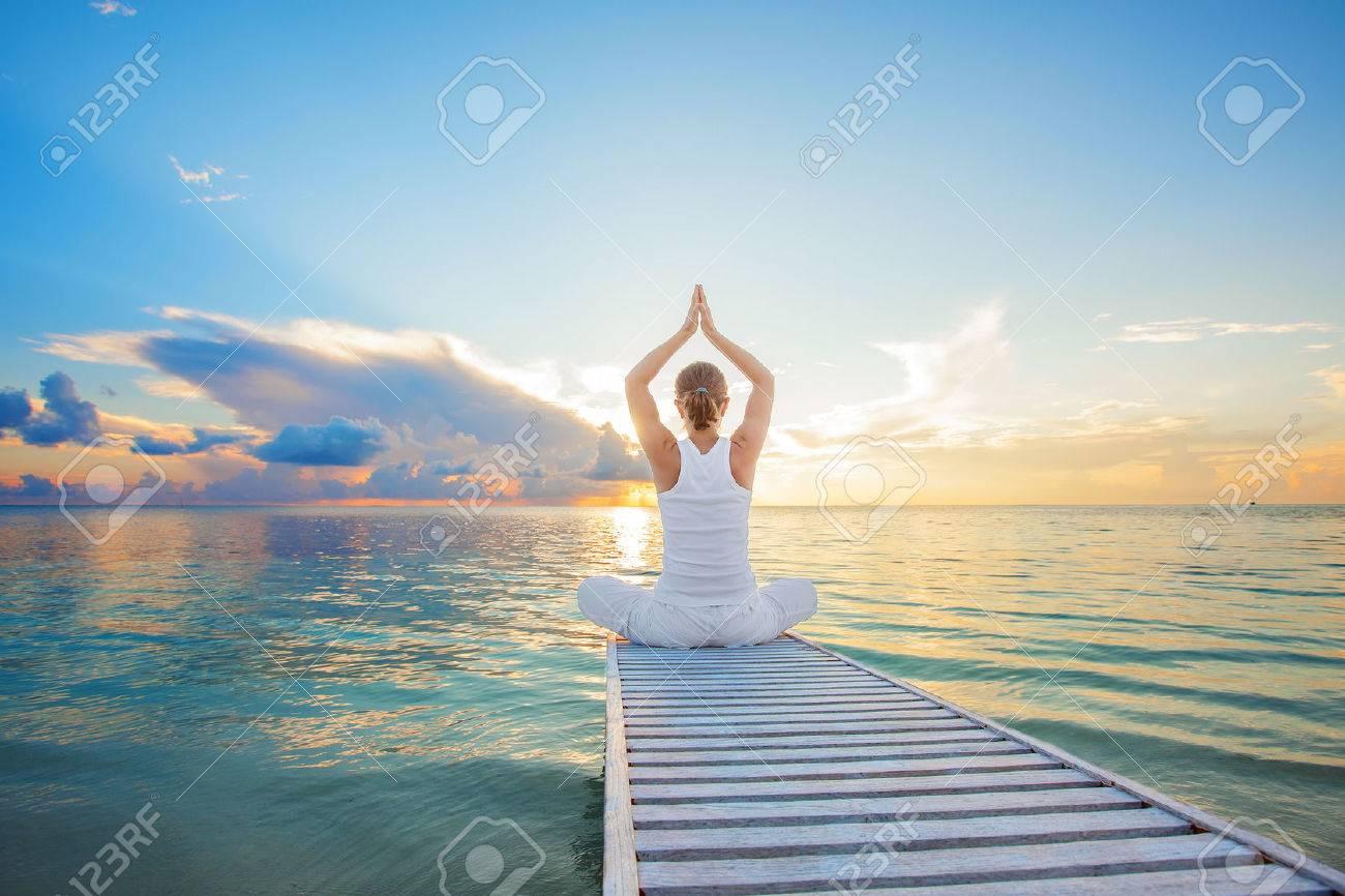 Caucasian woman practicing yoga at seashore - 22228289