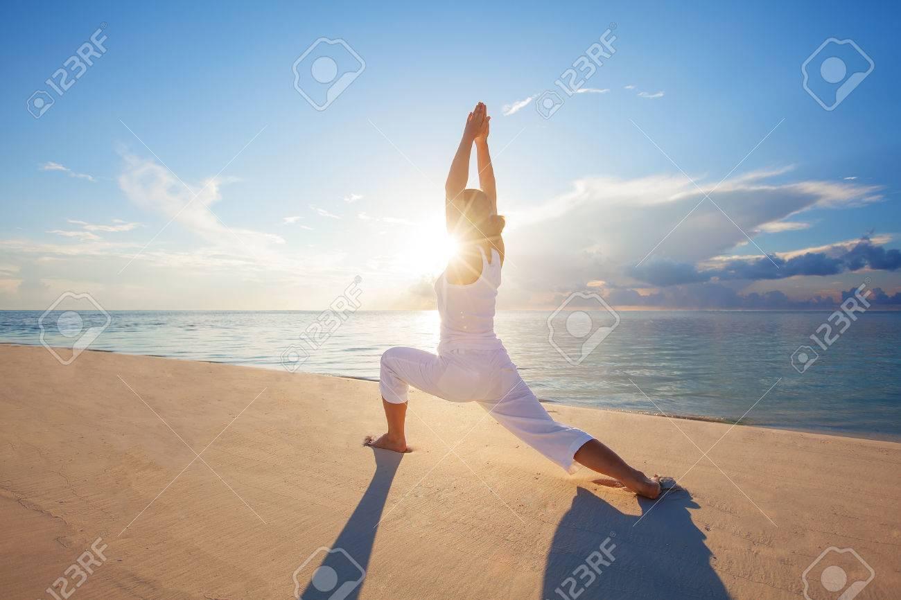 Caucasian woman practicing yoga at seashore - 22206892