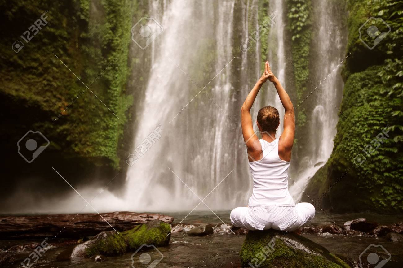 young woman doing yoga in a forest near waterfall - 35661038