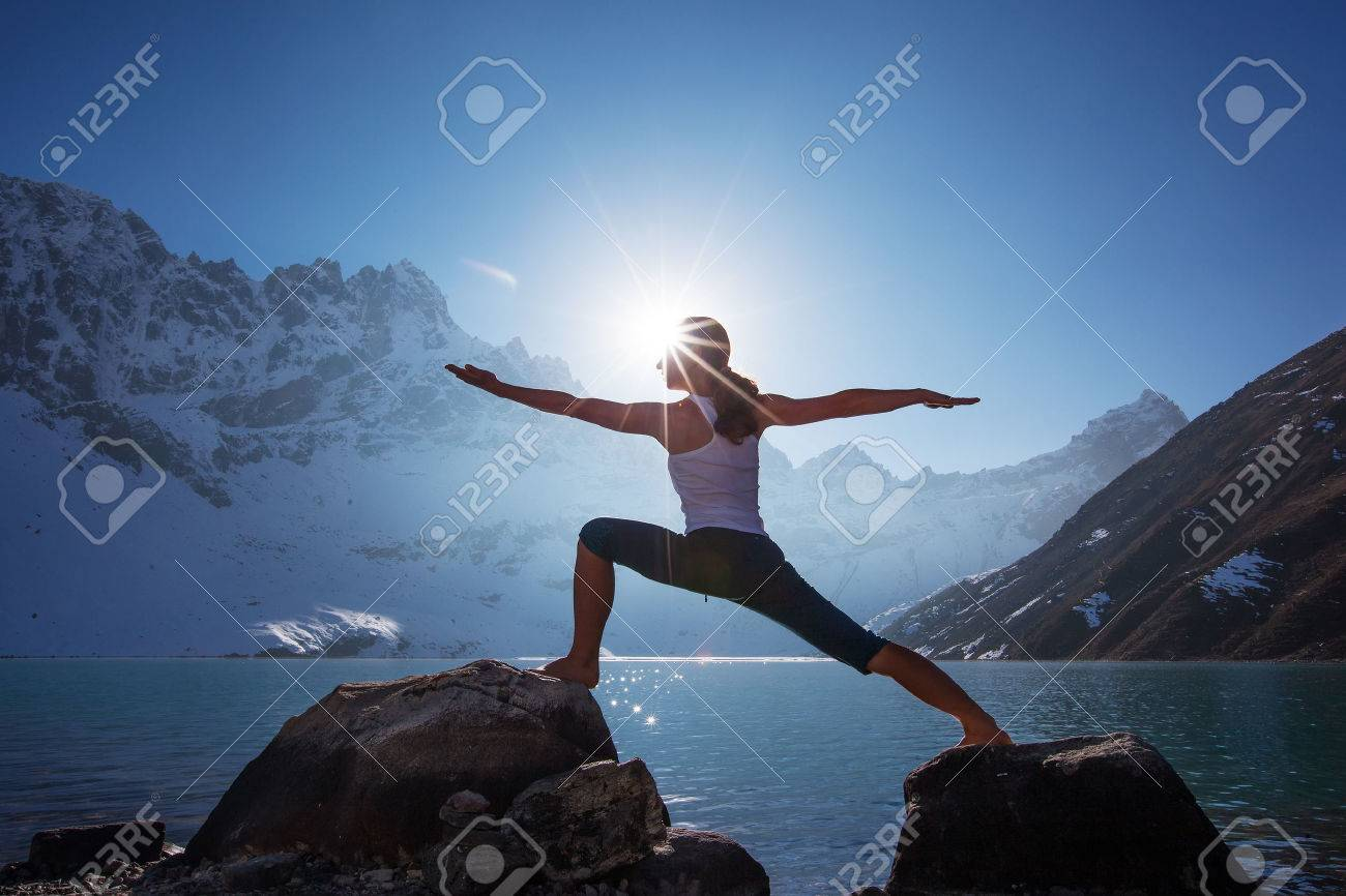 Young woman is practicing yoga at mountain lake - 35921631