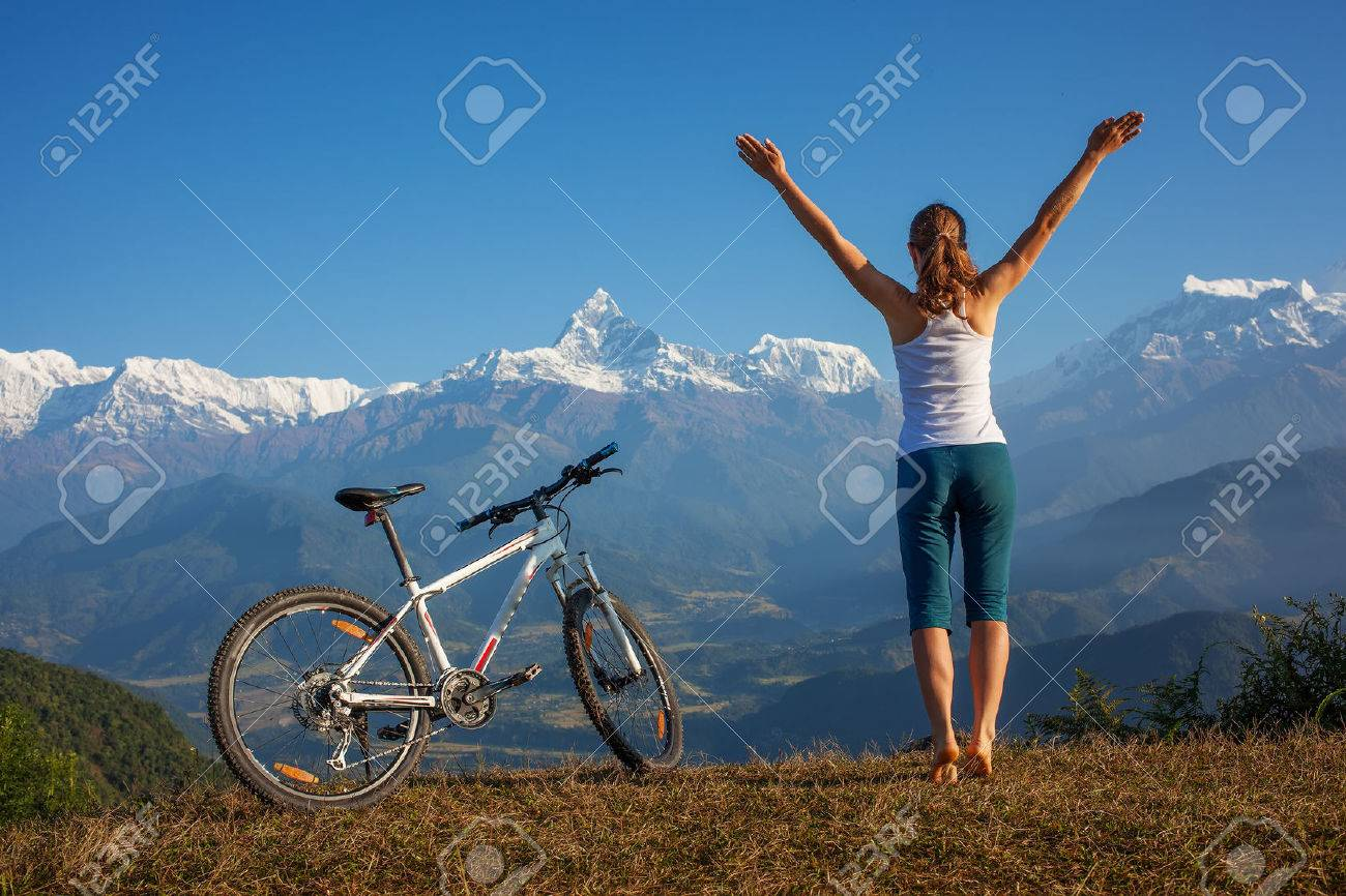 woman practicing yoga, relaxing after riding bikes high in mountain - 37191039