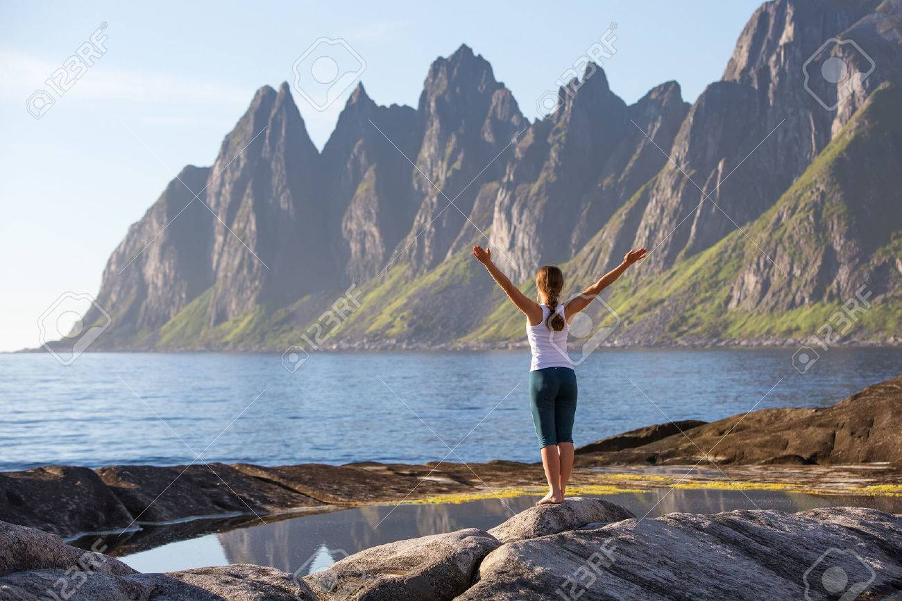 Young woman is practicing yoga between mountains in Norway - 40506421