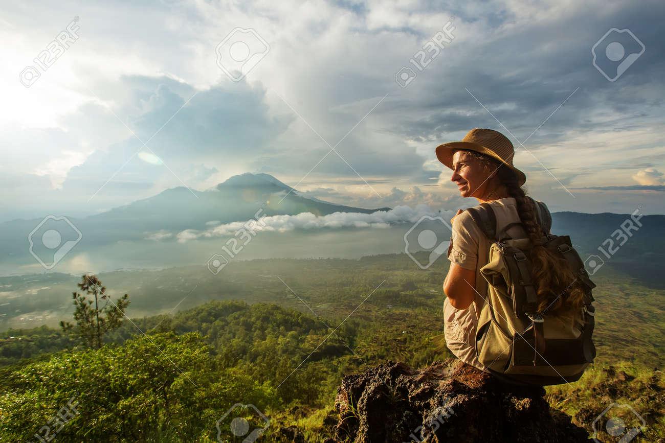 Woman enjoying sunrise from a top of mountain Batur, Bali, Indonesia. - 131159120
