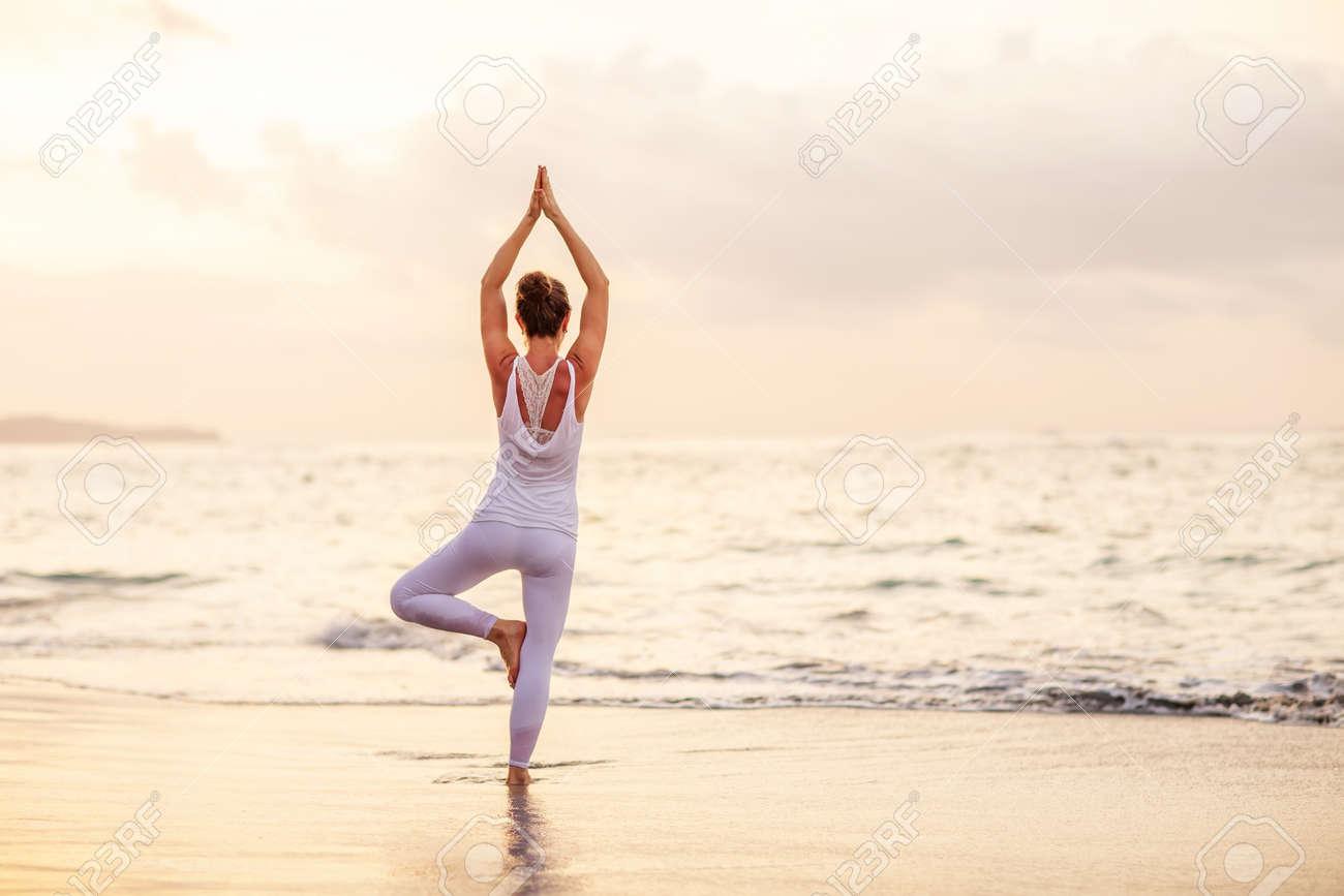 Woman practices yoga at seashore - 147184959