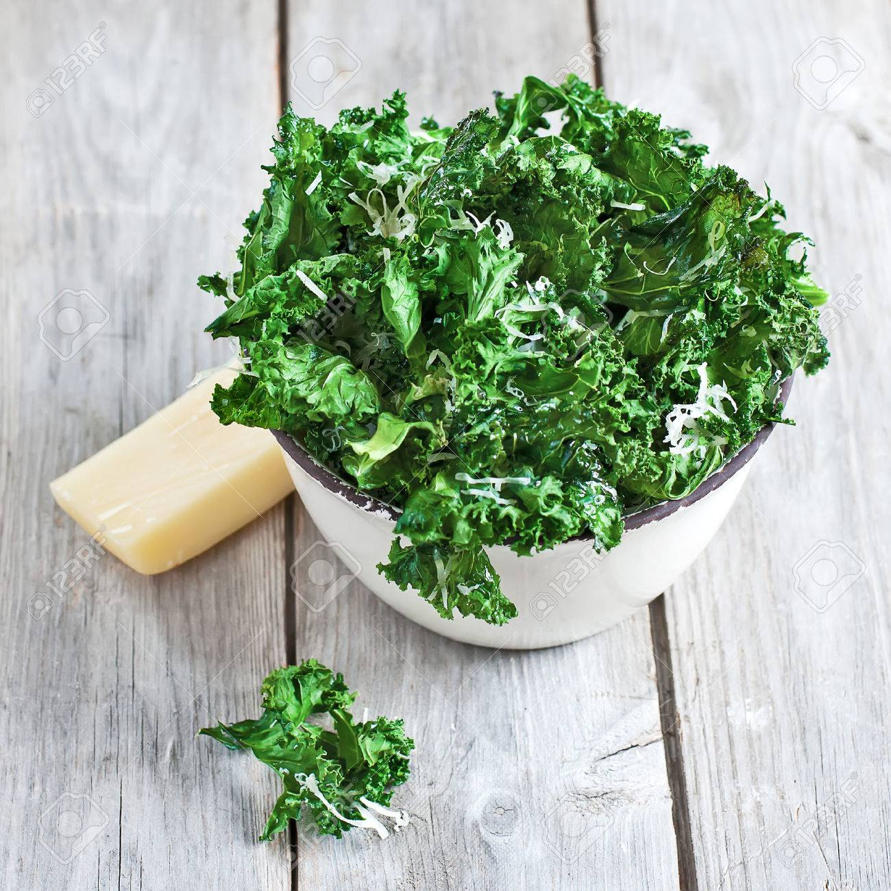 Kale chips with parmigano cheese in ceramic bowl. Selective focus. - 27910801