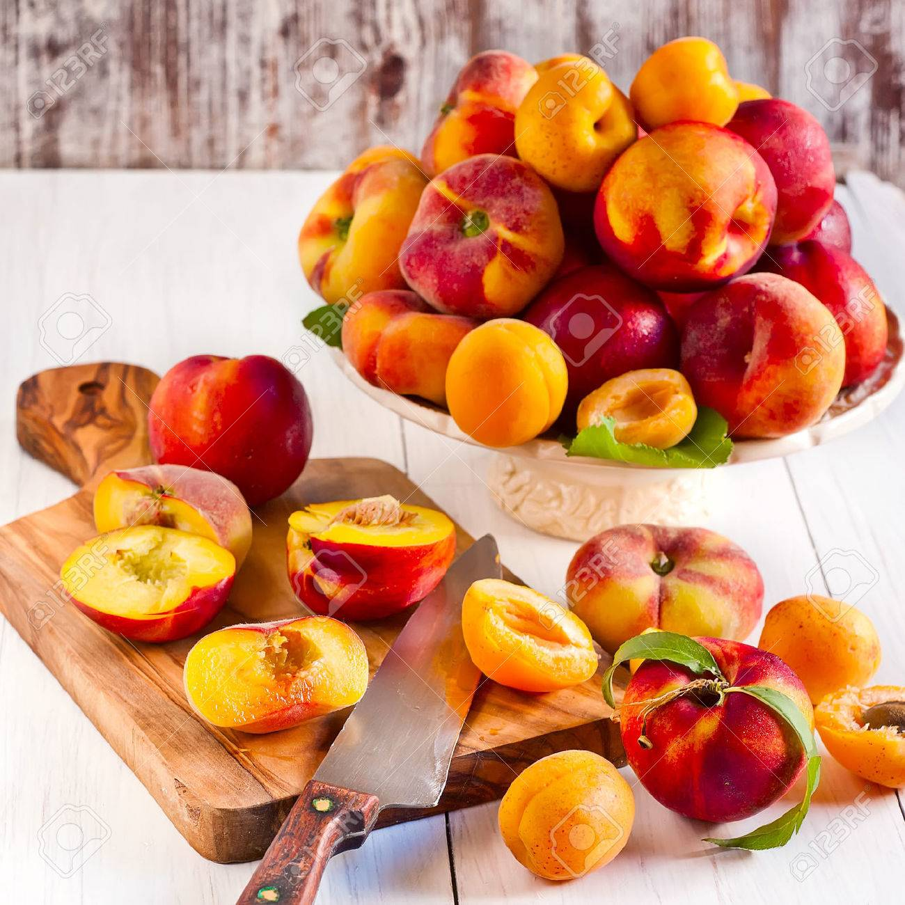 Ripe apricots, nectarines and saturn peaches on ceramic holder and olive wood desk with knife. - 29207544